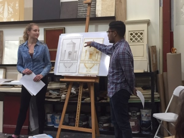 Two people presenting architecture design drawings.